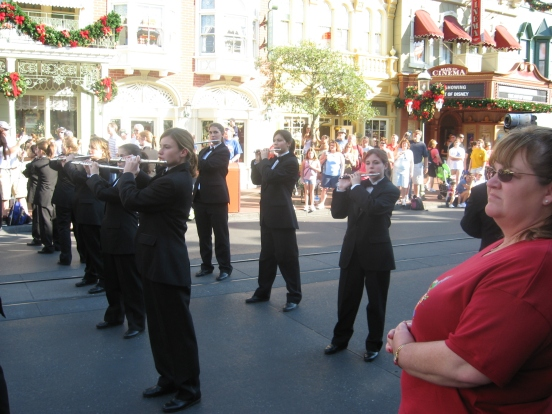 My daughter playing her piccolo while marching on Main Street USA again in 2007, back row last on right