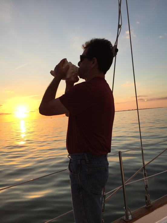 Ben blowing into the conch shell for the sunset