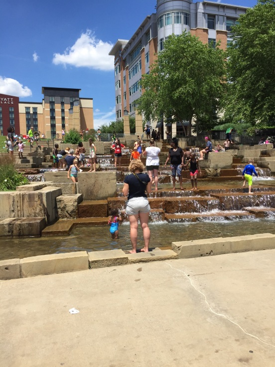 lots of families playing in the fountain