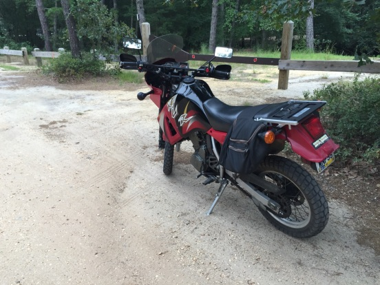 his bike is a Kawasaki KLR 650 - its street legal but also able to be taken off road.